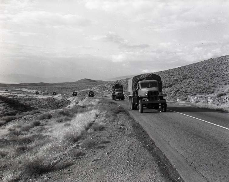 Multiple Army trucks drive on a rural Nevada road in 1941.