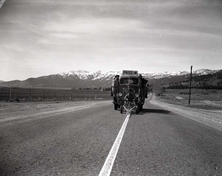 A car rides down the center of a two-lane road, striping a fresh white line in 1941.