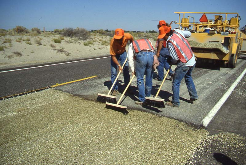 A team in orange hats and vests uses push brooms to pave the rural U.S. 50, September 1988.