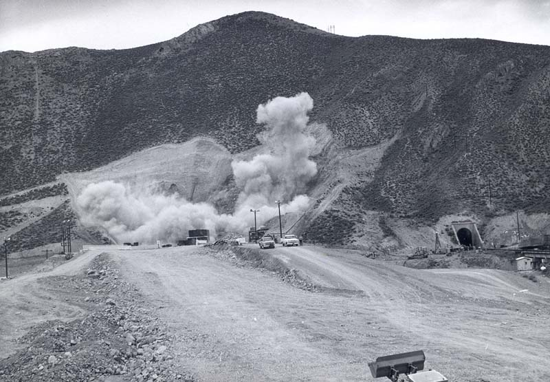 Dust erupts from a hillside as workers blast for the Carlin tunnels.