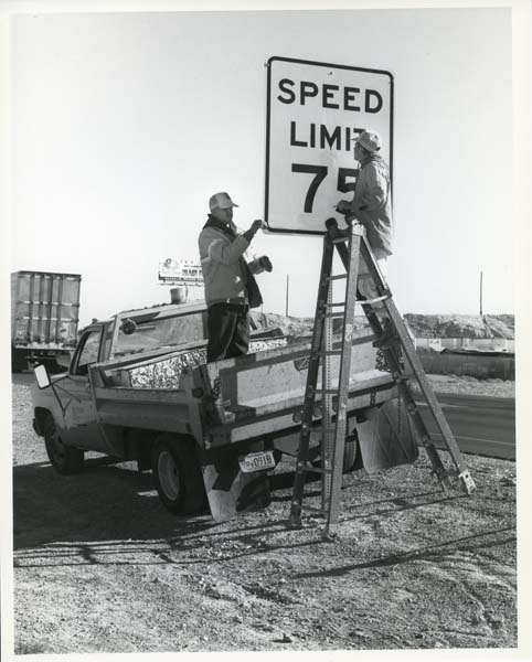 Maintenance workers are seen installing new speed limit signs in the early 1970's.
