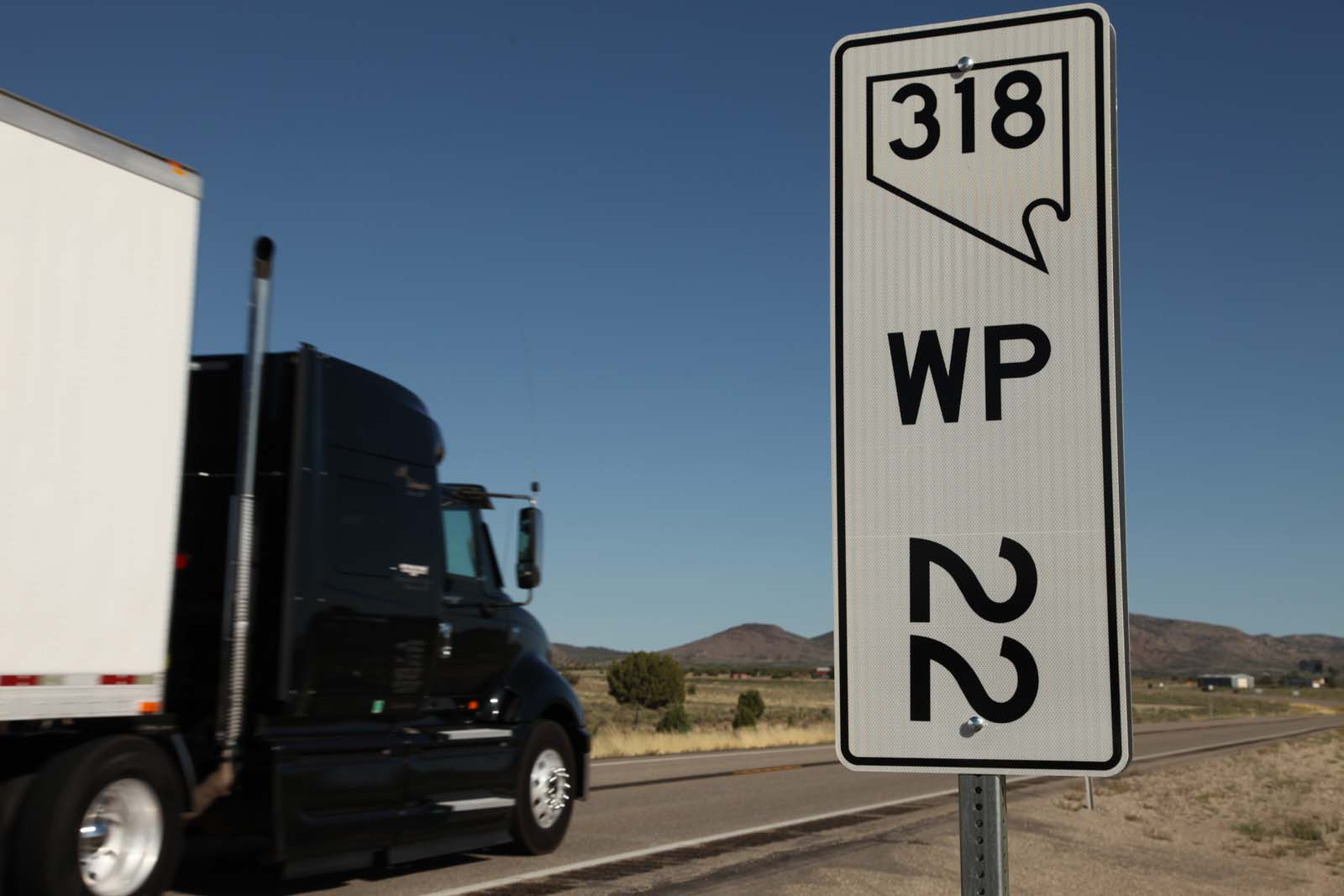 A freight truck drives through mile marker 22 in White Pine County