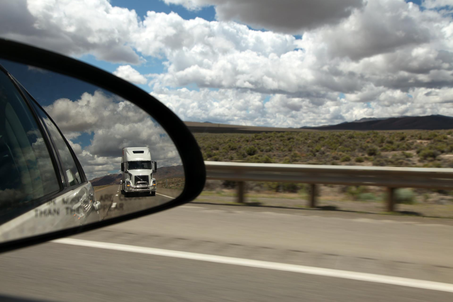 A freight truck as seen through the passenger-side mirror