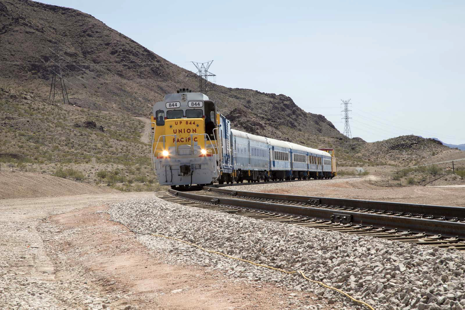 A Union Pacific train passes during the I-11 railroad bridge dedication ceremony