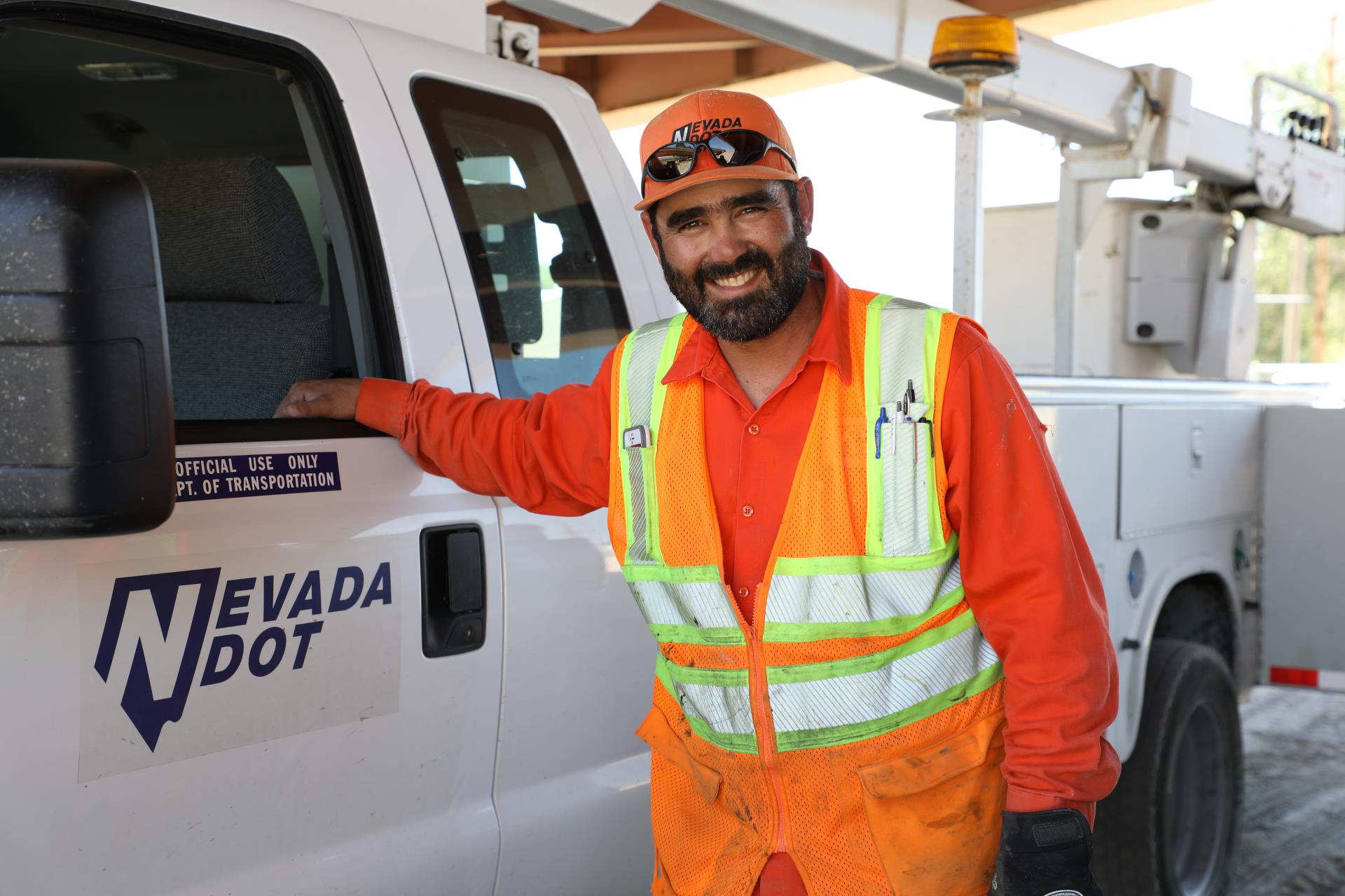 A photo of an NDOT maintenance professional posed with his NDOT vehicle
