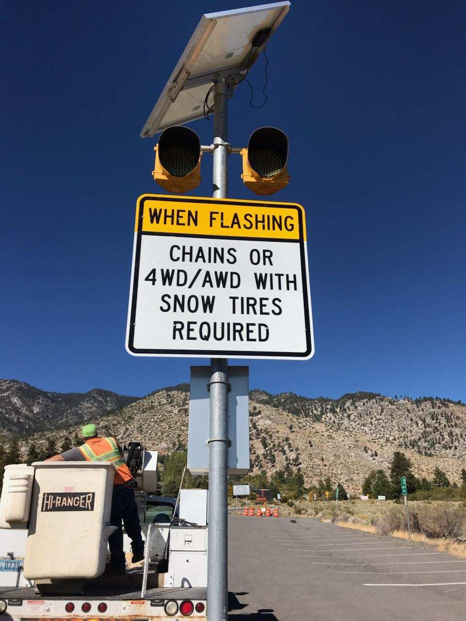 A sign displaying requirements for vehicles in winter weather