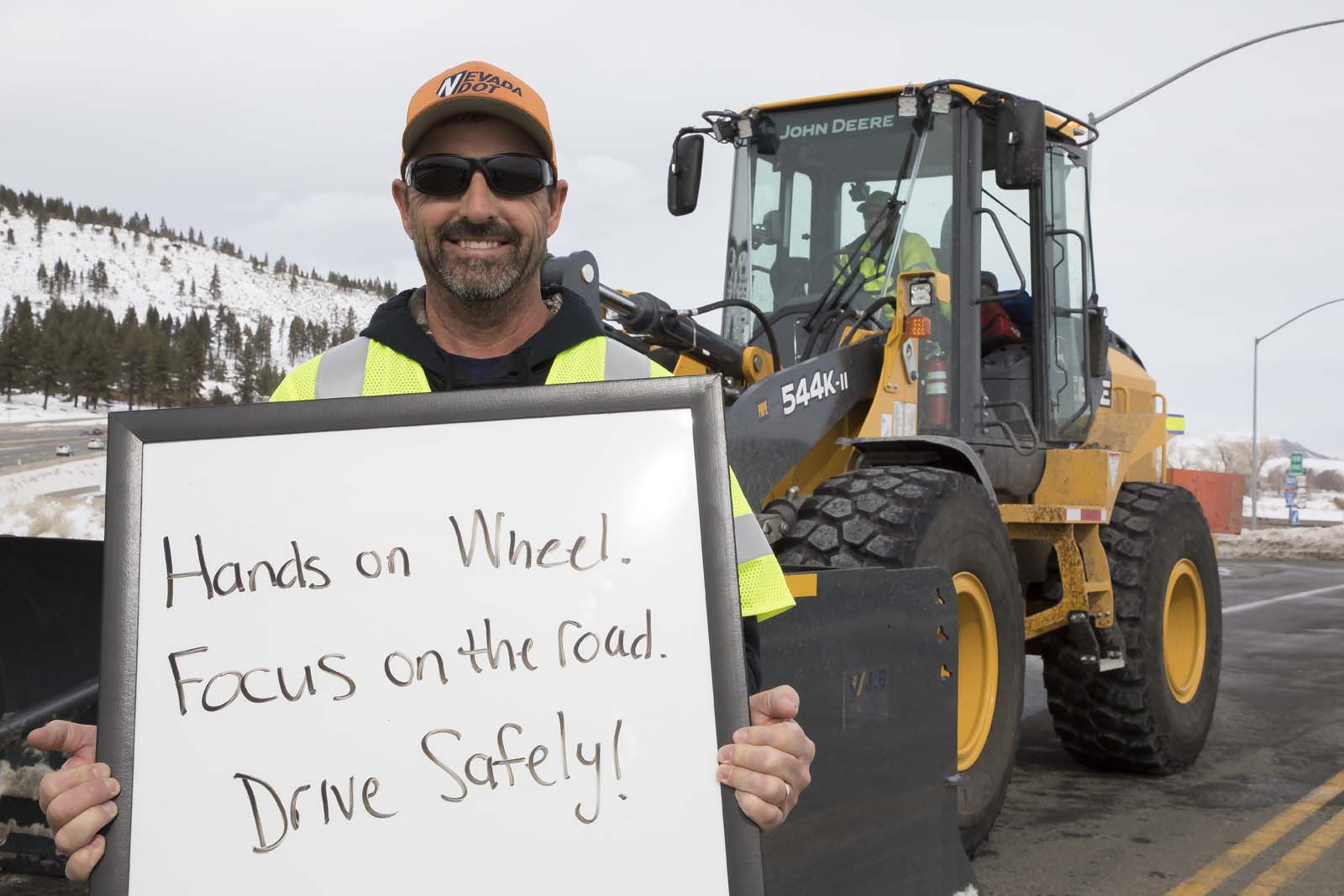 An NDOT employee holding a sign for drivers to slow down and drive safely