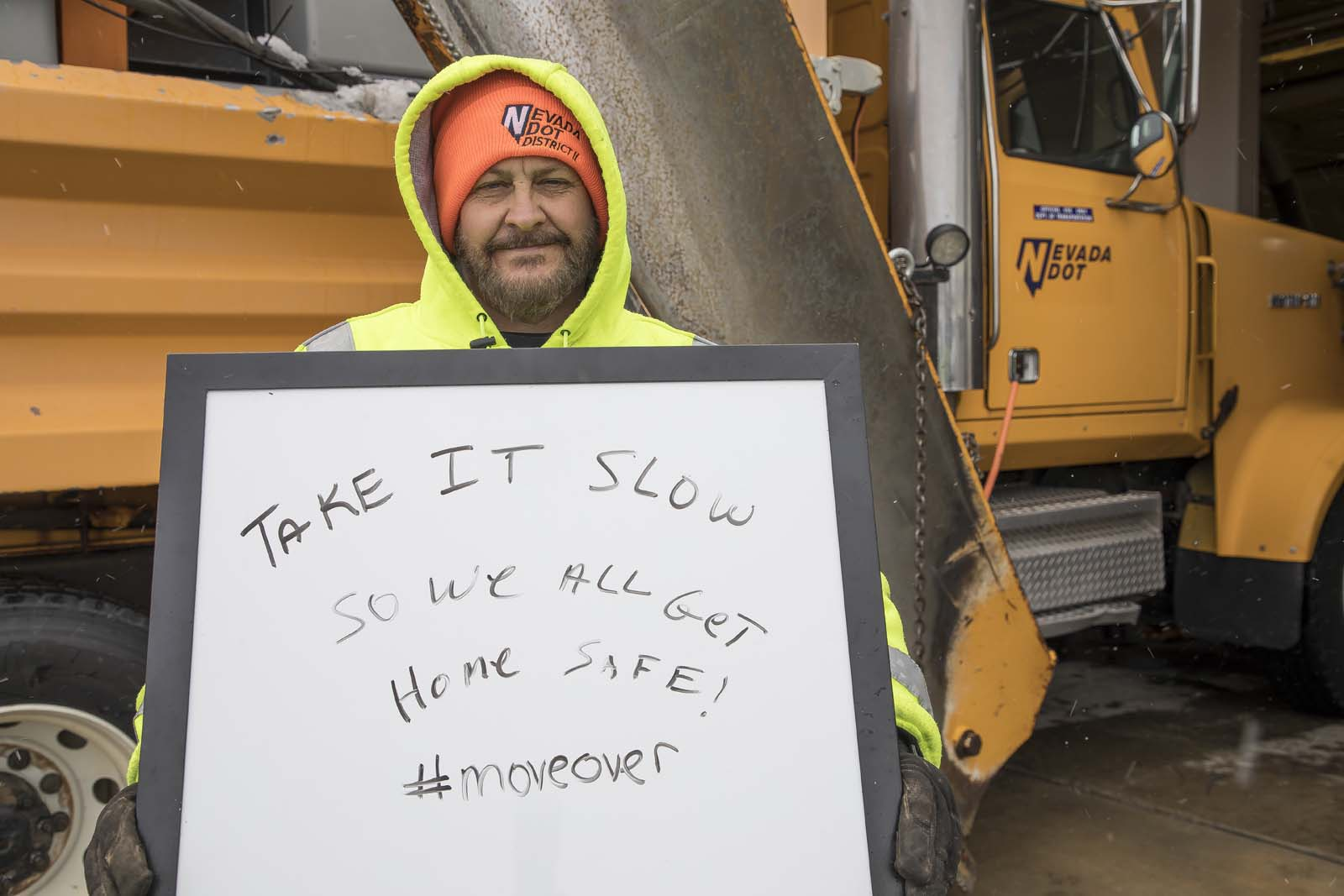 An NDOT employee holding a sign for drivers to go slowly in winter conditions