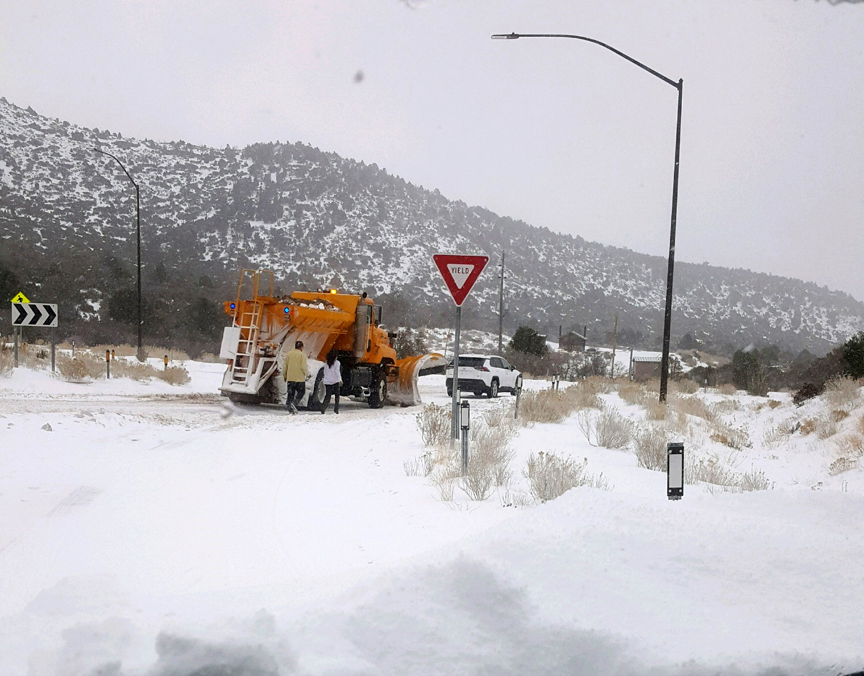 An NDOT plow assists a stranded vehicle at Mt. Charleston