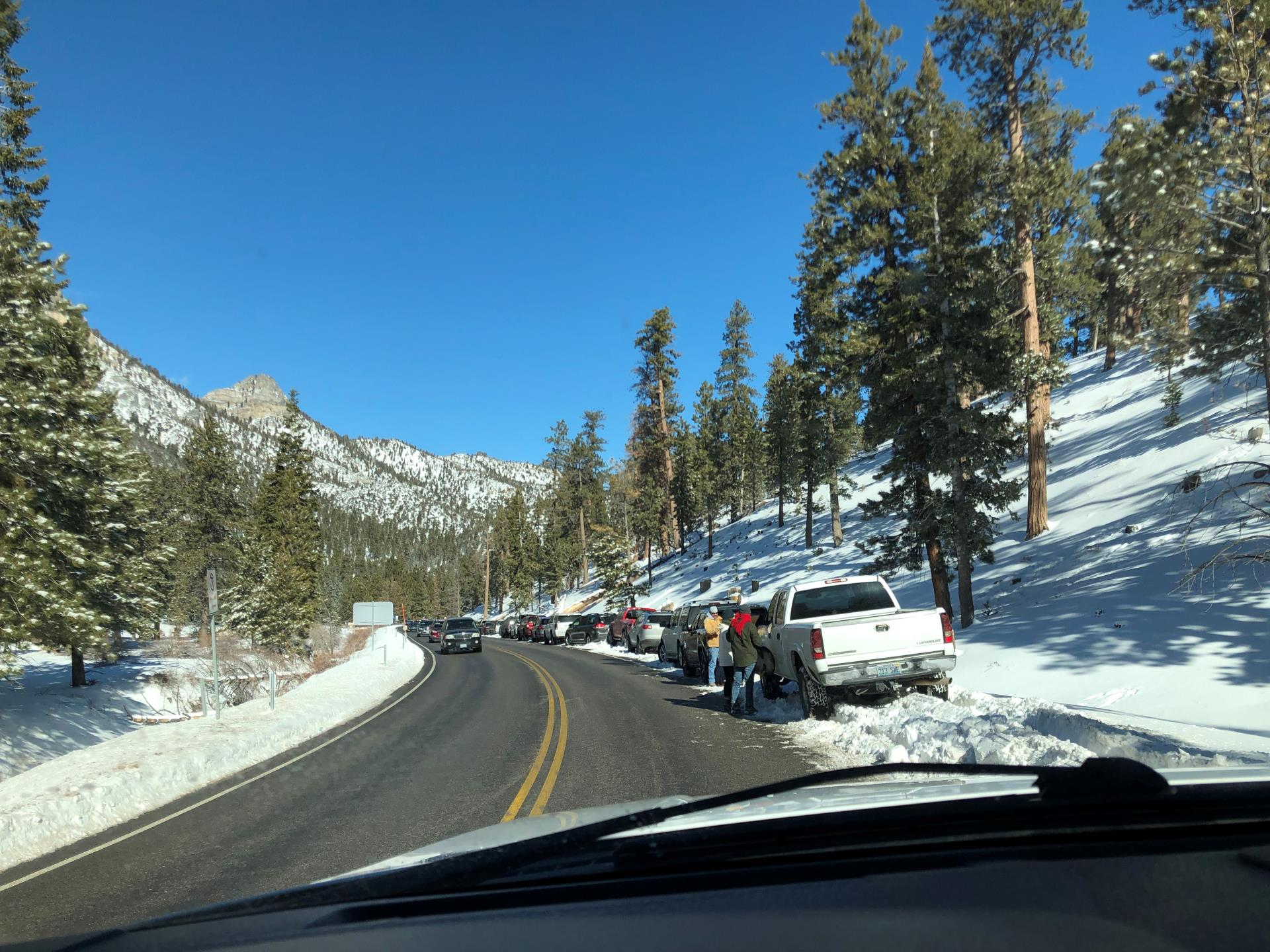 Cars parked along Mt. Charleston with snow on either side