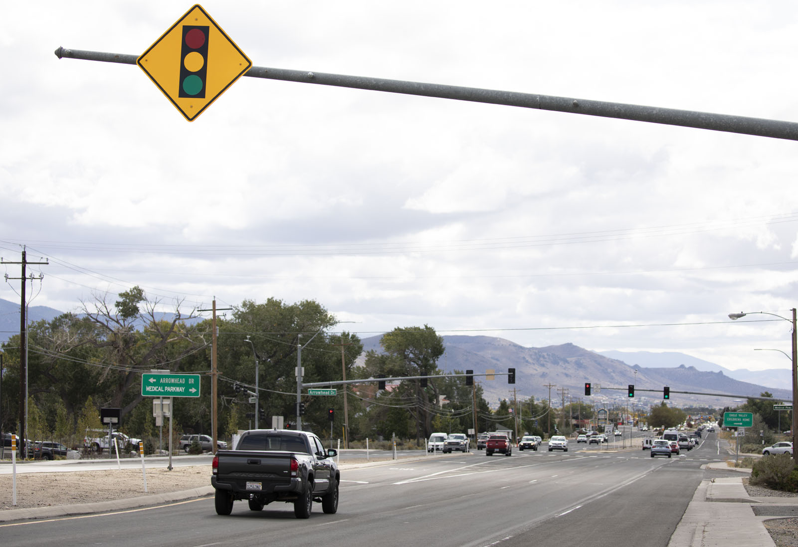 A car drives under a yellow road sign that signals a stoplight ahead