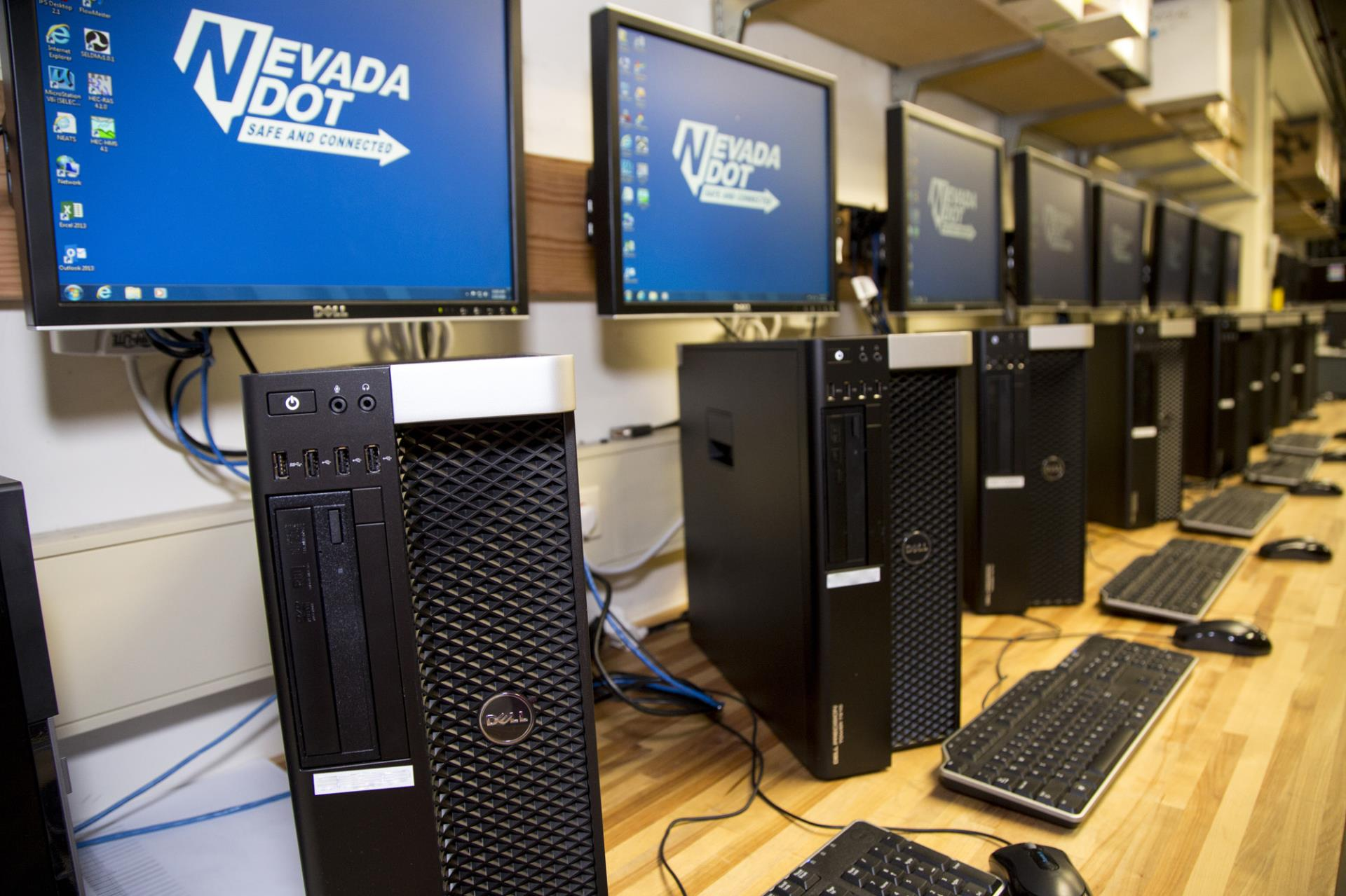 A row of computers with the blue NDOT logo on them