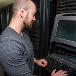 Photo of IT Employee accessing a computer terminal in the server room.